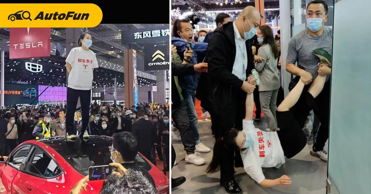 """สาวจีนสวมเสื้อสกรีน """"เบรกเจ๊ง"""" ประท้วง Tesla กลางงานเซี่ยงไฮ้ ก่อนถูกอุ้ม! (ชมคลิป) 01"""